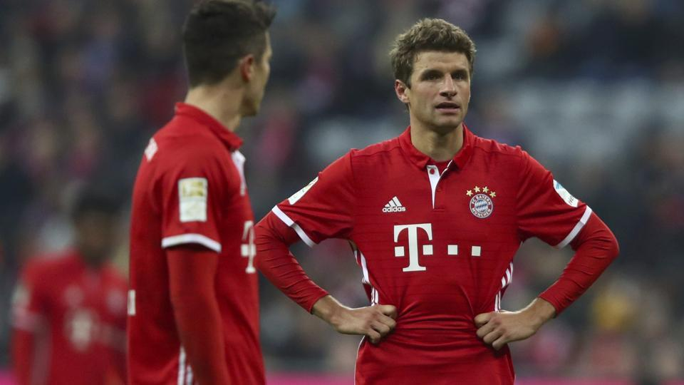 Robert Lewandowski and Thomas Muller of FCBayern Munich react at the end of the game against FCSchalke 04.