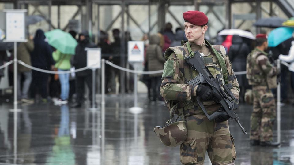 A French soldier patrols in the courtyard of the Louvre museum with the visitor control in background in Paris.