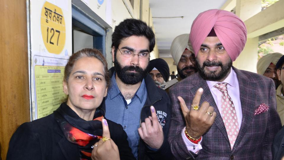 Navjot Singh Sidhu with his wife, former MLA Navjot Kaur Sidhu. and son Karan Sidhu, showing their inked fingers after casting their votes at a polling both in SR Government College, Amritsar, on Saturday, February 4.