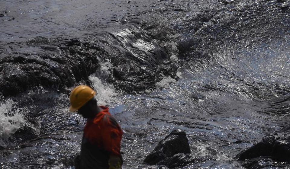 A firefighter stands beside a thick oily tide from the sea lapping the coast, after an oil tanker and an LPG tanker collided off Kamarajar Port in Ennore, in Chennai on Febuary 4.