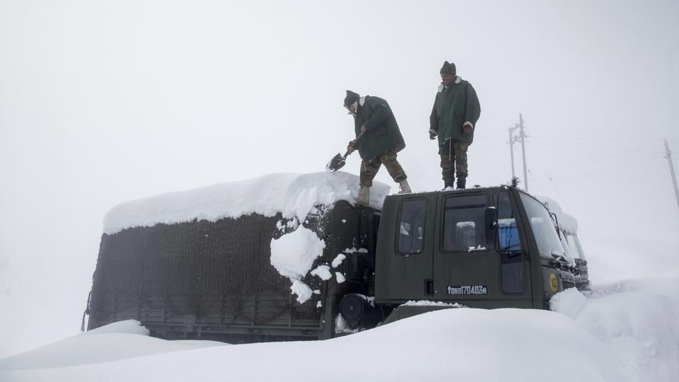 Indian Army soldiers clear snow from their stranded vehicle near a base camp in Gulmarg in Kashmir on Jan 27, 2017.  Authorities have issued avalanche warnings for many parts of Kashmir and Himachal Pradesh, as the heavy snowfall has cut off roads, disrupted power and communication lines, and forced the evacuation of hundreds of residents.