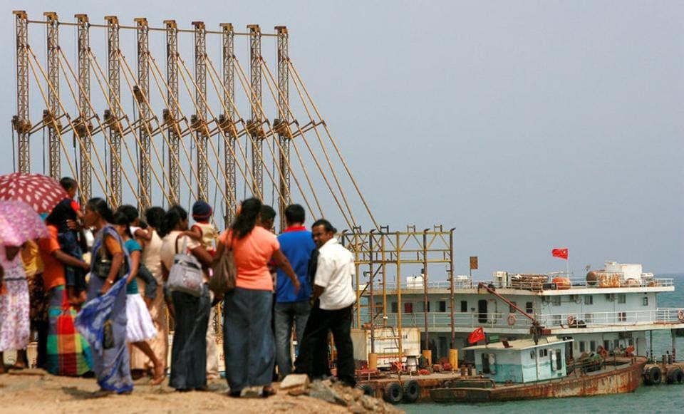 People watch Chinese dredging ships work at Hambantota.