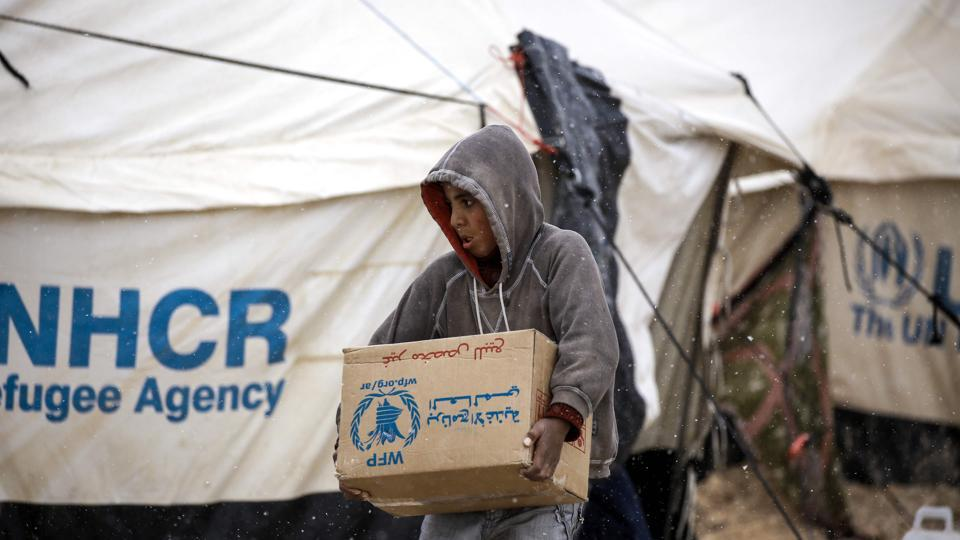 A displaced Syrian child carries a humanitarian aid relief box as he walks through the snow in a refugee camp in al-Hawl, located some 14 kilometers from the Iraqi border in Syria's northeastern Hassakeh province. Refugee resettlement organisations are bracing for significant funding cuts and possible layoffs over the coming months during US President Donald Trump's temporary refugee ban.
