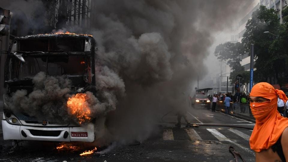 Civil servants protesting against austerity measures clash with riot police and set fire to a bus on Rio Branco, the main avenue in Rio de Janeiro, Brazil, while firefighters attempt to put out the blaze.   (VANDERLEI ALMEIDA / AFP)