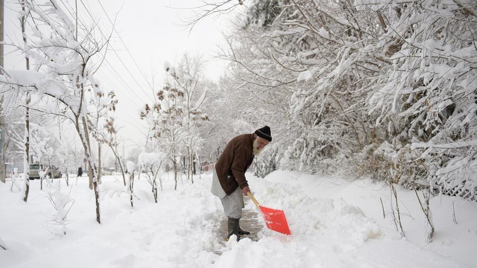 An elderly Afghan man shovels snow in Kabul on Sunday. Avalanches and freezing weather have killed more than 20 people in different areas of Afghanistan, officials said on Saturday, as rescuers worked to save scores still trapped under the snow.