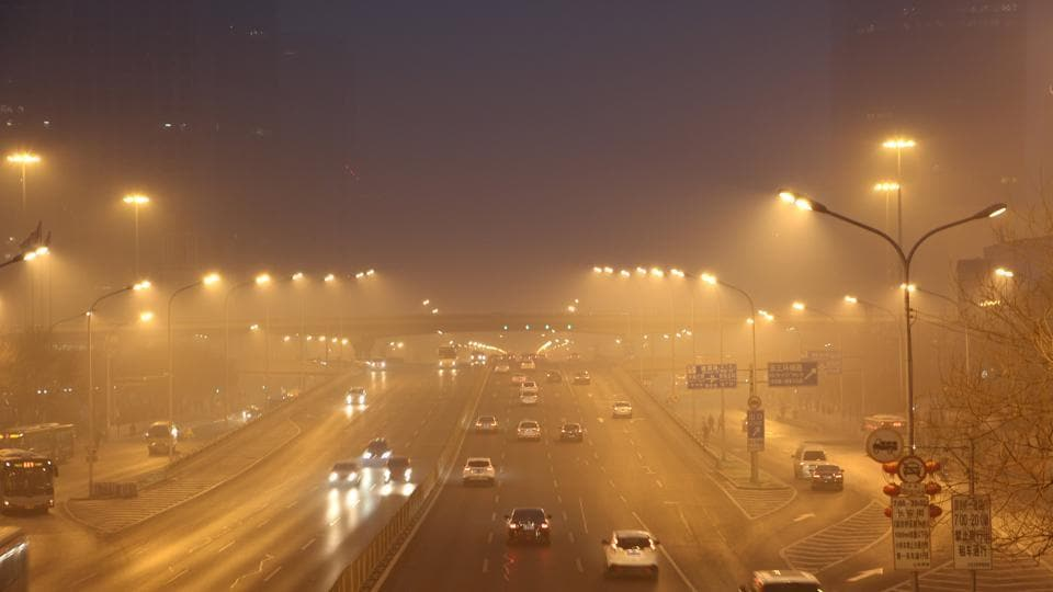 Cars drive along a street in smog during a polluted day in Beijing, China.