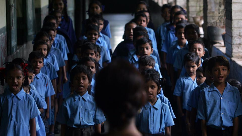 Schoolchildren sing national anthem.