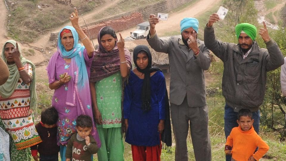 Residents of Masol village showing their inked fingers after casting their vote.