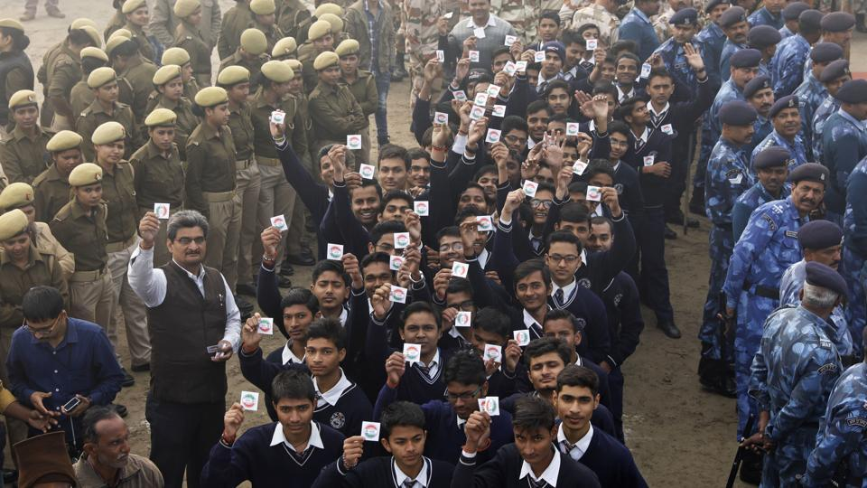 Students hold up badges urging people to cast their votes, during an election awareness campaign in Allahabad.