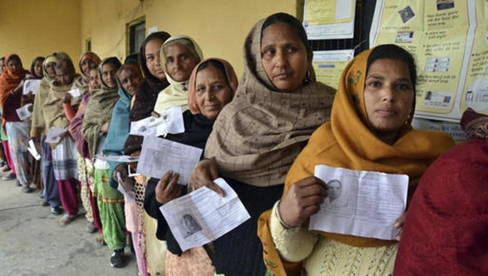 Voters display their election identity cards as they stand in a queue to cast their votes outside a polling station, at Chogawan village, about 20 kilometers from Amritsar, in the northern Indian state of Punjab.