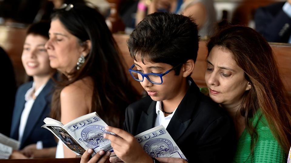 These two read a book on horse racing at the racecourse on Sunday. (Kunal Patil/Hindustan Times)