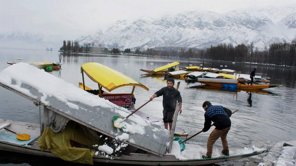 People removing snow from their Shikara in Srinagar.