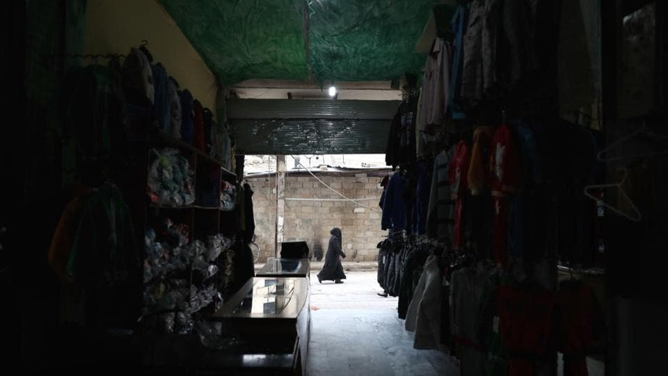 A Syrian woman walks past a workshop. (Abd Doumany/AFP)