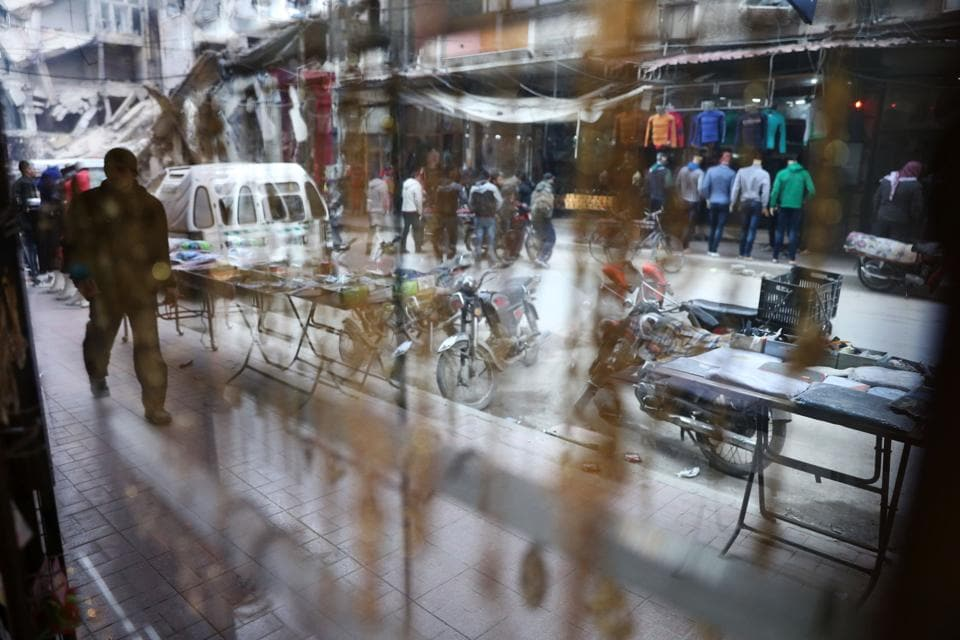 A picture taken from inside a shopfront shows a Syrian man walking in Douma. (Abd Doumany/AFP)