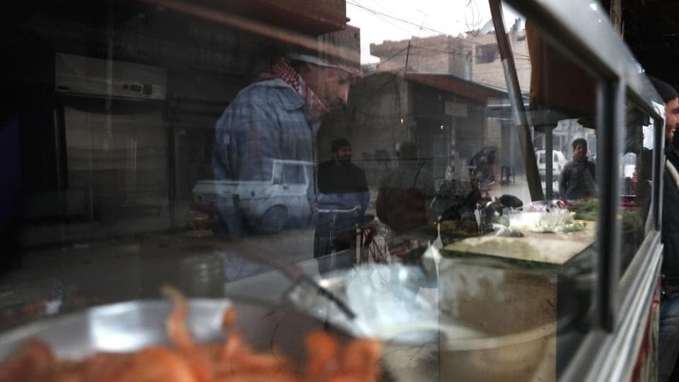 The reflection of Syrian men is seen as they shop for food. (Abd Doumany/AFP)