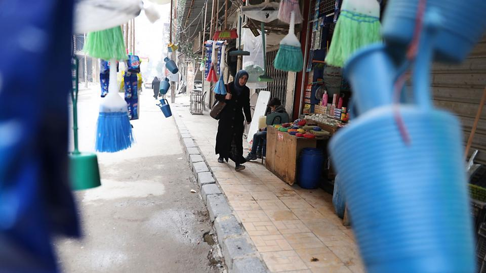 A Syrian woman walks past brooms and plasticware. (Abd Doumany/AFP)