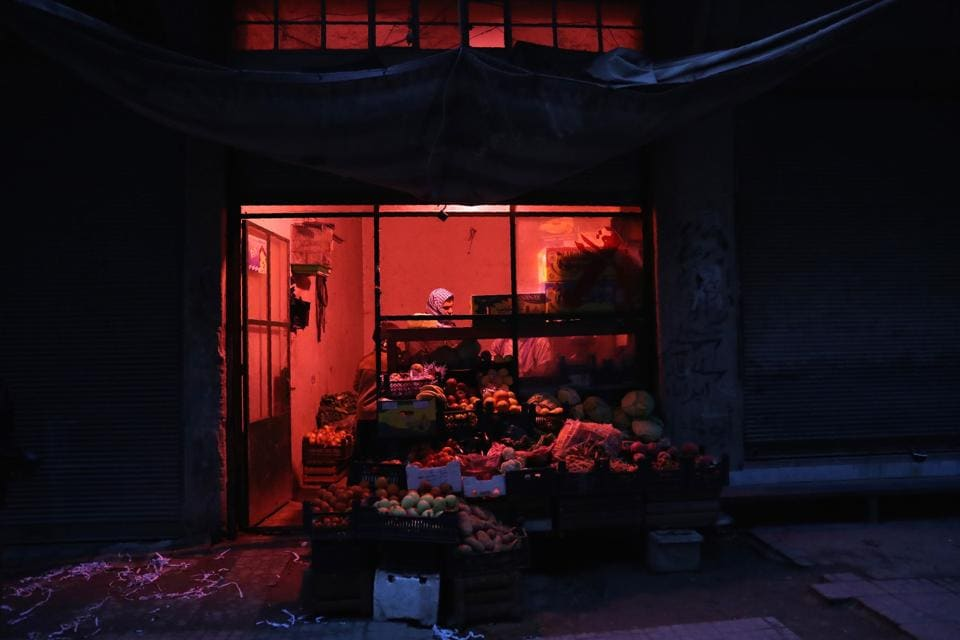 A Syrian vendor works at a vegetable and fruits shop at night. (Abd Doumany/AFP)