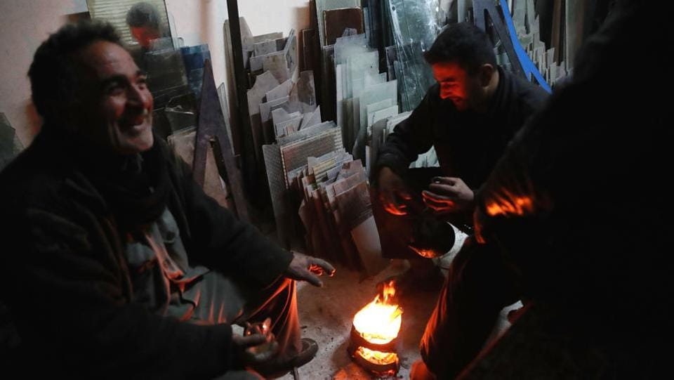 Syrian men sit around a fire at a glass-workshop. (Abd Doumany/AFP)