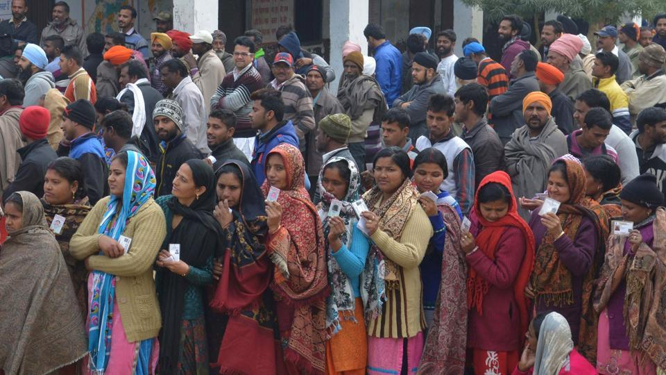 Voters pose for photographers as they queue to at a polling booth in a village on the outskirts of Amritsar.