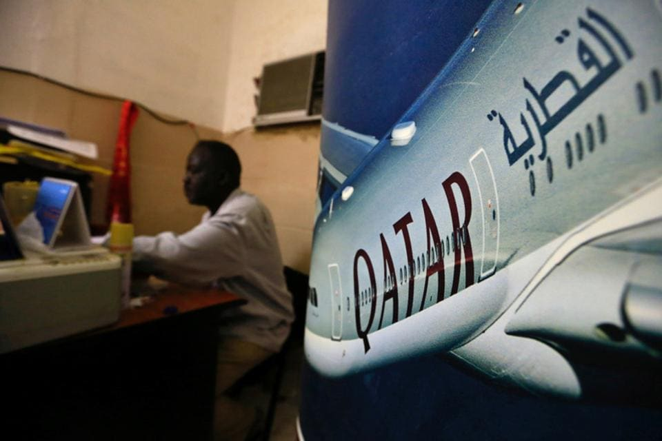 An image of a Qatar Airways plane is seen near an employee working at a travel agency in Khartoum, Sudan.