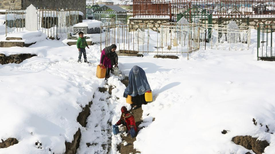 A woman and her children carry containers of water in the snow on the outskirts of Kabul, Afghanistan, on Monday.