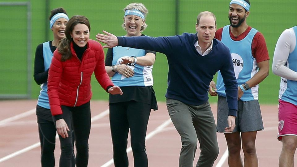 Prince William holds up his arm in an attempt to block his wife Kate, the Duchess of Cambridge, as they line up for a relay race during the promotion of the charity Heads Together  at the Queen Elizabeth II Park in London.  (REUTERS)