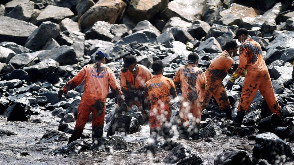 Firefighters and volunteers try to clean up oil that has washed ashore, in Chennai.