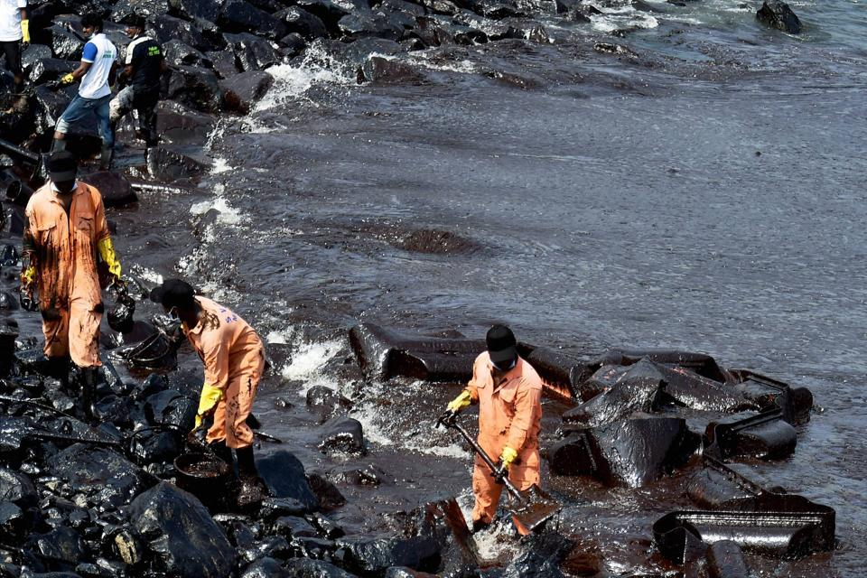 Firefighters and volunteers clean up the oil that washed ashore in Chennai after an oil tanker and an LPG tanker collided off Kamarajar port in Ennore.
