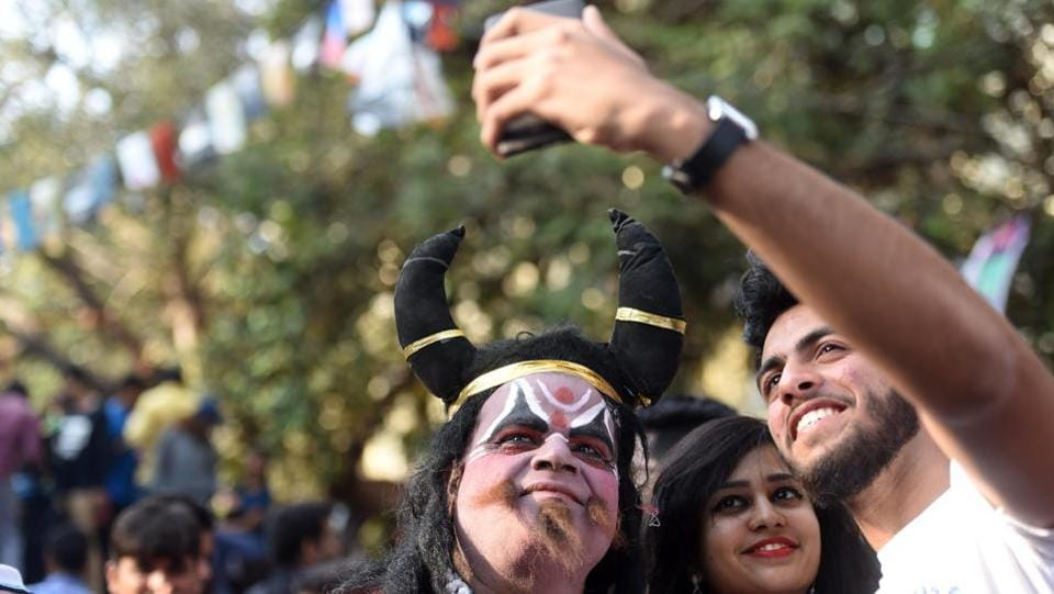 People takes selfies with a man dressed as Yamraj, god of death. (Pratik Chorge/HT )