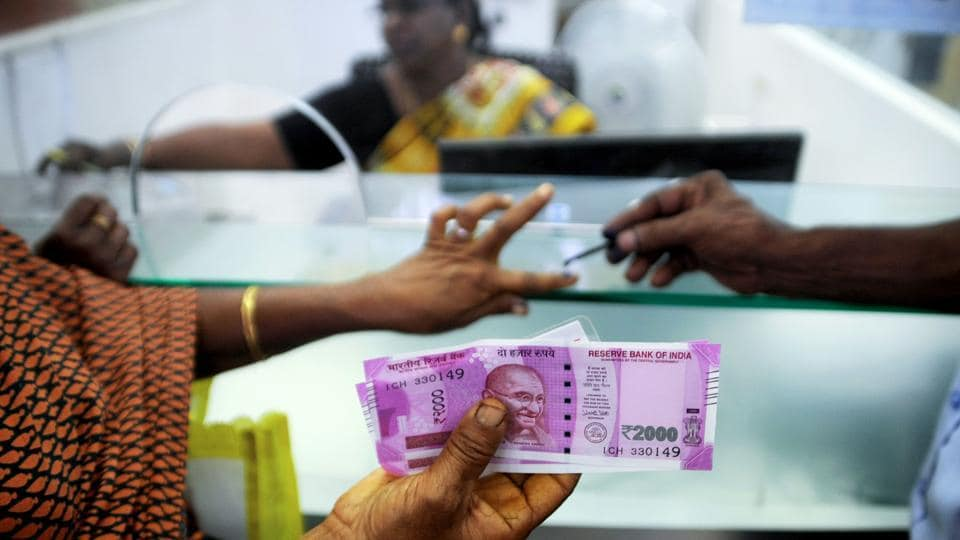 In this photograph taken on November 17, 2016, a woman holds Rs 2000 notes as she has her finger marked with indelible ink after exchanging Rs 500 and Rs 1,000 banknotes at a bank in Chennai.