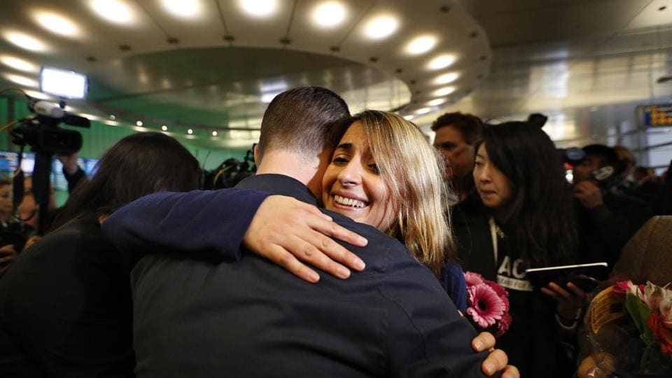 California student Sara Yarjani (R) receives a hug from a friend after arriving at the Tom Bradley International Terminal at Los Angeles International Airport on Sunday.