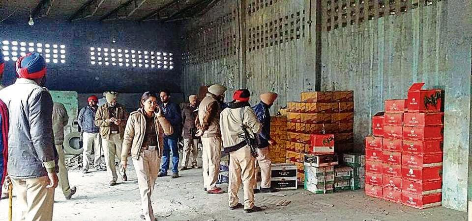 Police officials inspecting the illegally stored cartons of liquor in Jalandhar.