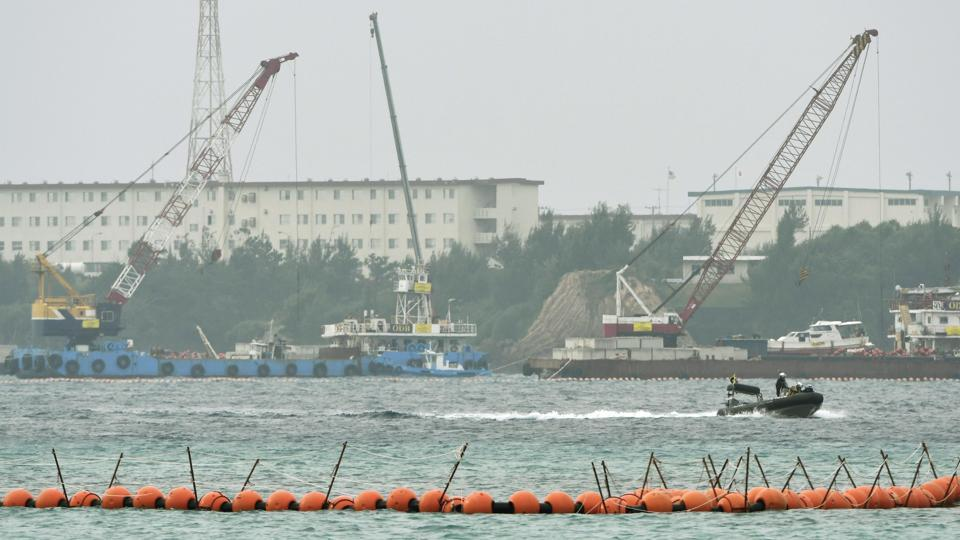 A boat goes by cranes being used for the preparation work to relocate a US Marine base to Henoko to dump large concrete blocks into sea along the shore in Nago, Okinawa Prefecture, southern Japan. Japan's government has started offshore construction work on relocating a US Marine base on Okinawa.
