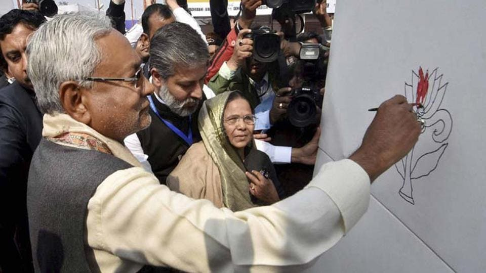 Nitish Kumar fills colour on a painting of lotus drawn by famous Madhubani painter Bahua Devi during inauguration of the Patna Book fair on Saturday.