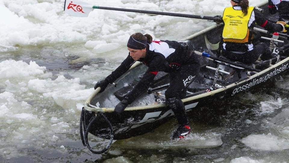 Team Financiere Banque Nationale takes part in the ice canoe race on the Saint Lawrence river as part of the Quebec Winter Carnival in Quebec.  (AP)