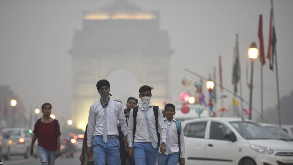 School students cover their face with handkerchieves to avoid thick smog at the Rajpath in evening.