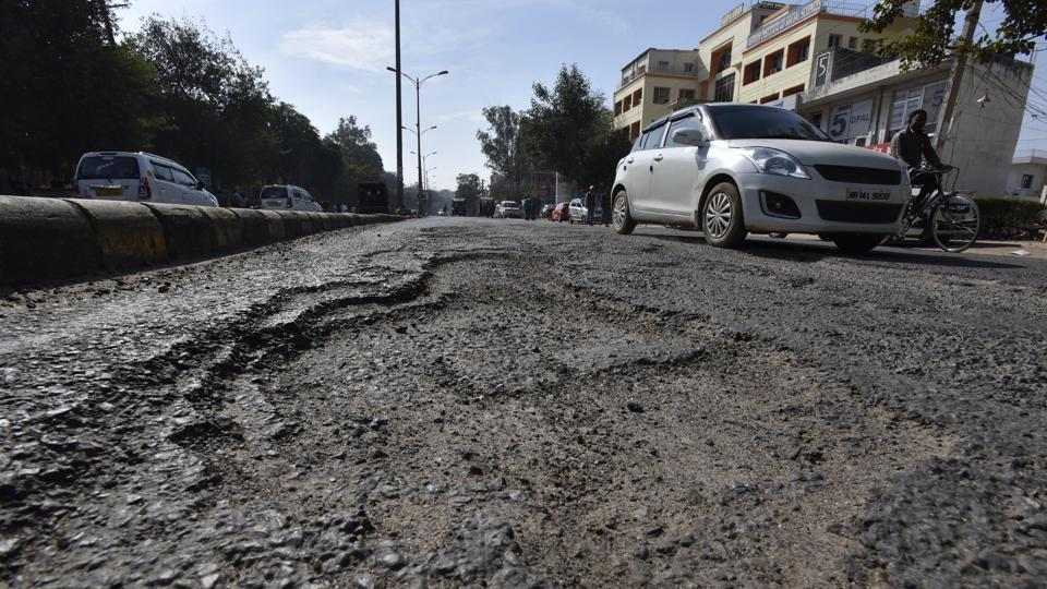 A pothole riddled stretch between the bus stand and Iffco Chowk on  MG Road on Tuesday.