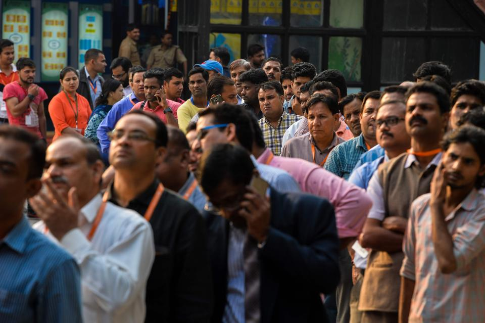 Indian people wait in a queue to withdraw money from a mobile ATM machine in New Delhi on November 15, 2016. India is to use indelible ink to prevent people from exchanging old notes more than once, the government said, a week after the withdrawal of high-value banknotes from circulation in a crackdown on