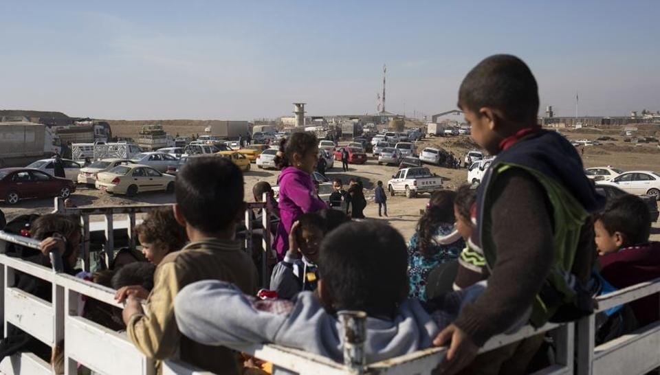 Children wait on the back of a pick up truck outside the Khazer checkpoint on the road to Mosul, Tuesday Feb. 7, 2017. T