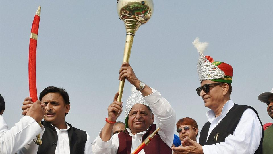 Samajwadi Party patriarch Mulayam Singh Yadav holds a mace as Uttar Pradesh chief minister Akhilesh Yadav and PWD minister Azam Khan during an event in Unnao of UP. Father Mulayam Singh has agreed to campaign for son Akhilesh Yadav as the battle for the UP throne grows intense.