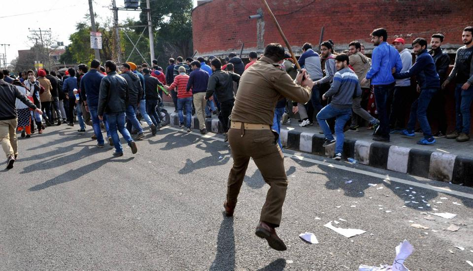 A policeman disperses protesters during a rally in Jammu.