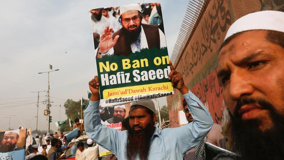 A supporter of Jamaat-ud-Dawah carries a poster to protest the house arrest of Hafiz Saeed in Karachi.