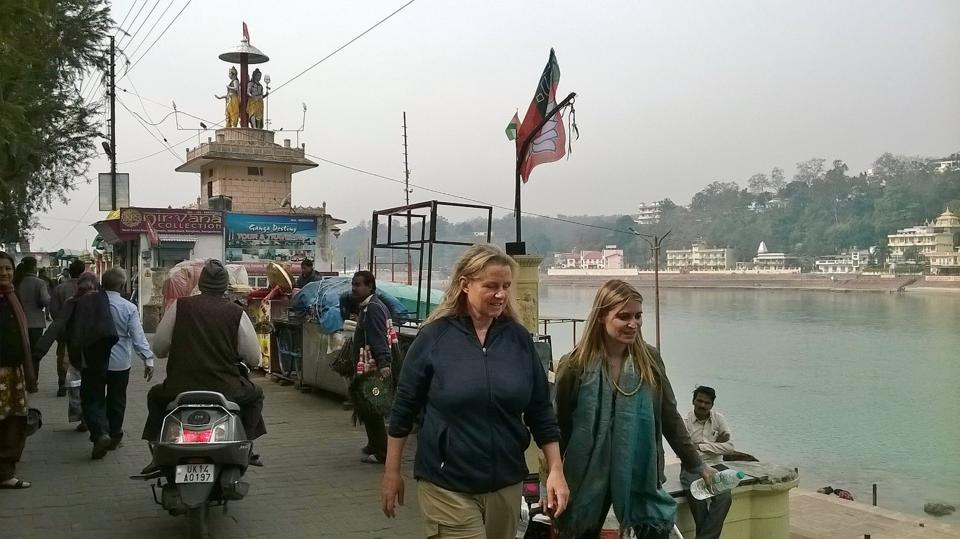 Foreigners pass by a political rally in Rishikesh.