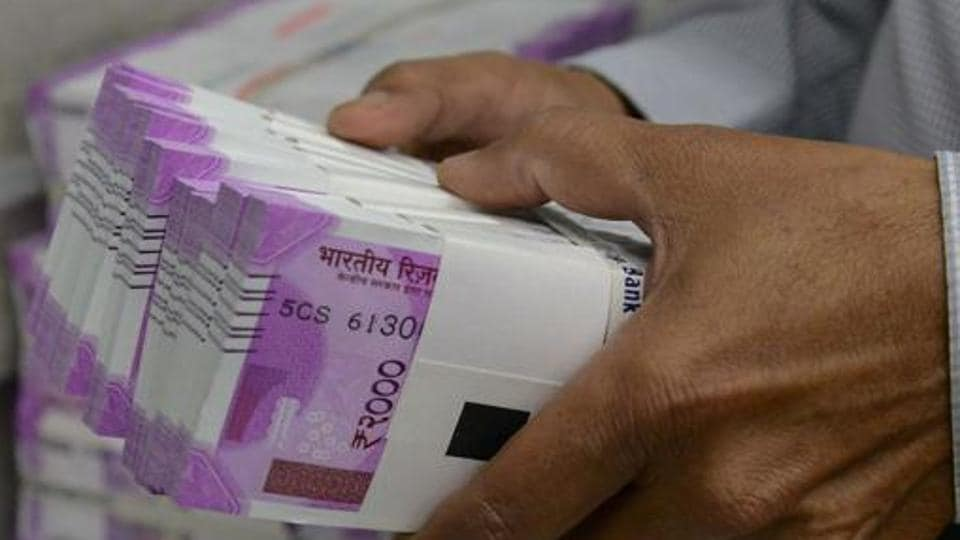 An Indian bank employee checks stacks of new 2000 rupee notes in Ahmedabad on November 11, 2016.