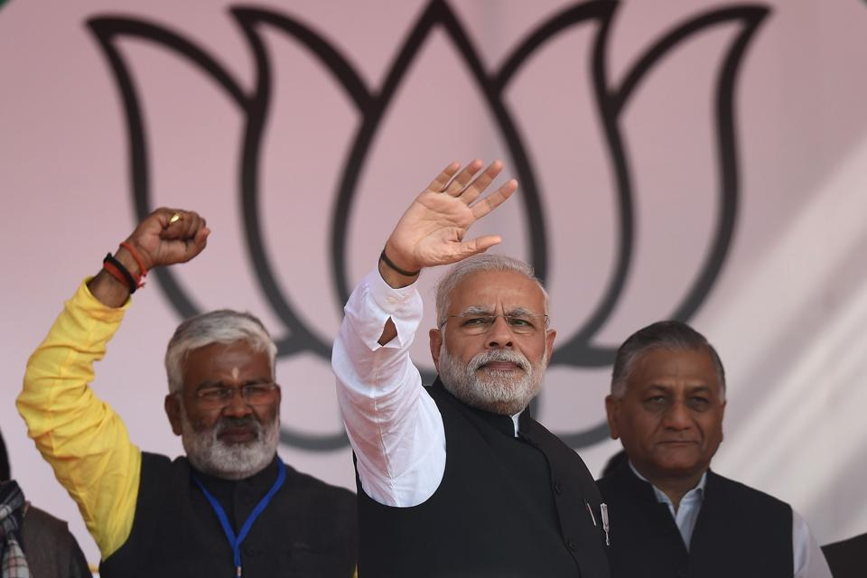 Prime Minister Narendra Modi waves after delivering a speech during a state assembly election rally in Ghaziabad on February 8, 2017.