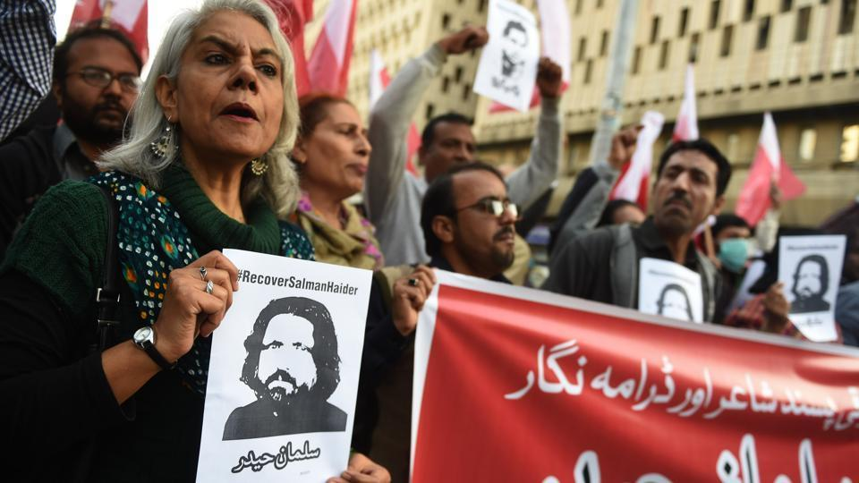 Pakistani rights activists hold images of bloggers who had gone missing during a protest in Peshawar on January 10, 2017.