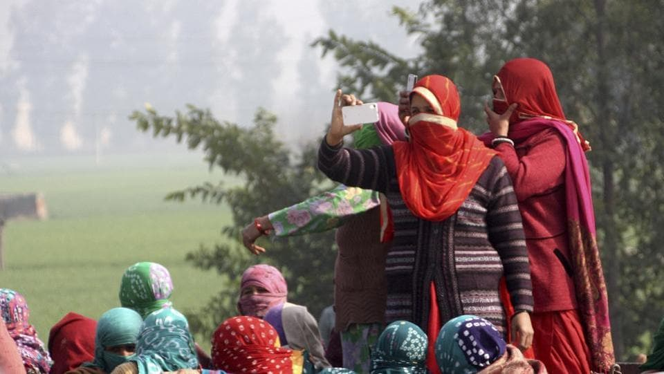 Protesters click photographs of security forces deployed along the protest site in Jassia village . (Manoj Dhaka / ht photo )