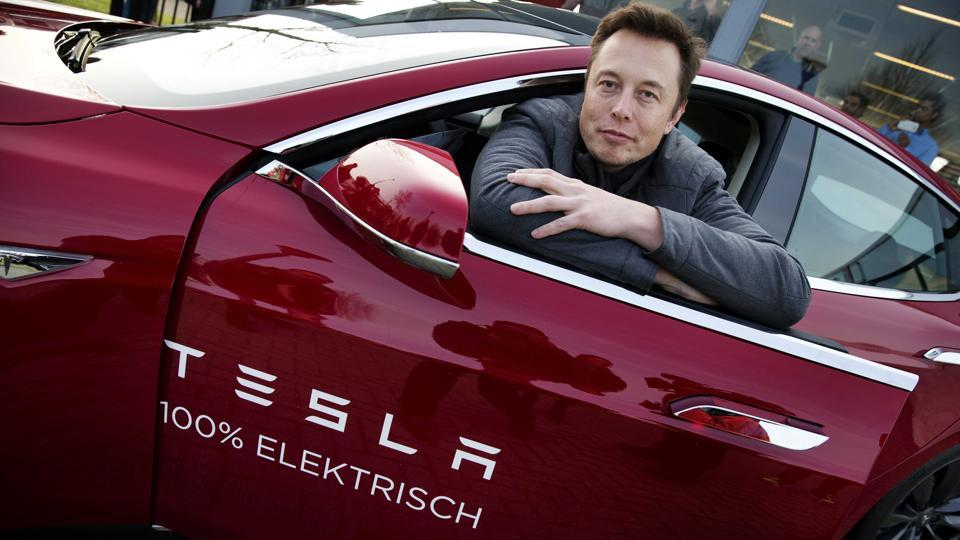 Elon Musk, co-founder and CEO of Tesla, poses with a model of the brand during a visit to Amsterdam.
