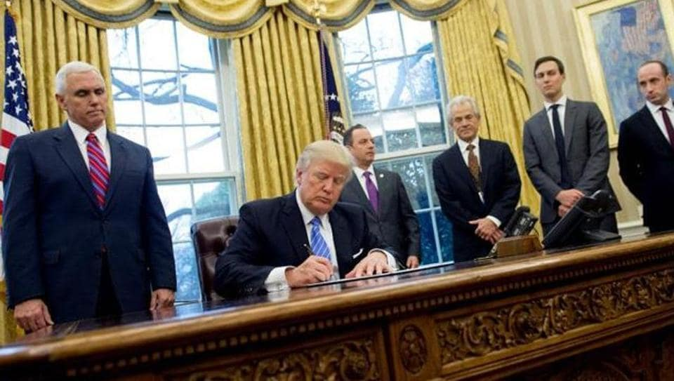 US President Donald Trump signs an executive order in the Oval Office of the White House in Washington, DC, on January 23.