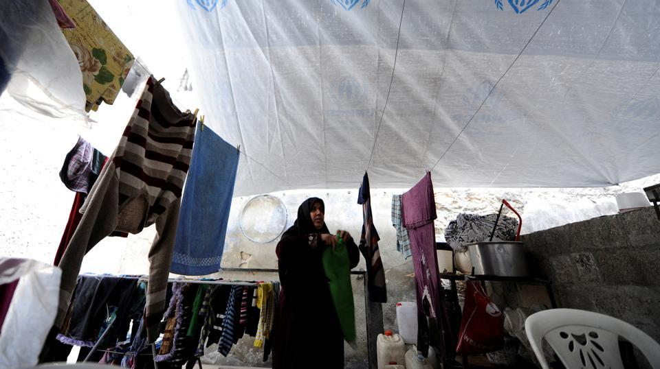 Heyam Batash, 56, hangs clothes at her house in al-Mouassassi street in Aleppo, Syria, January 30.